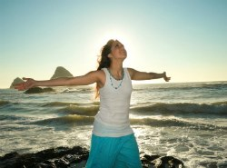 Woman on beach with open arms conveys a feeling of joy and freedom